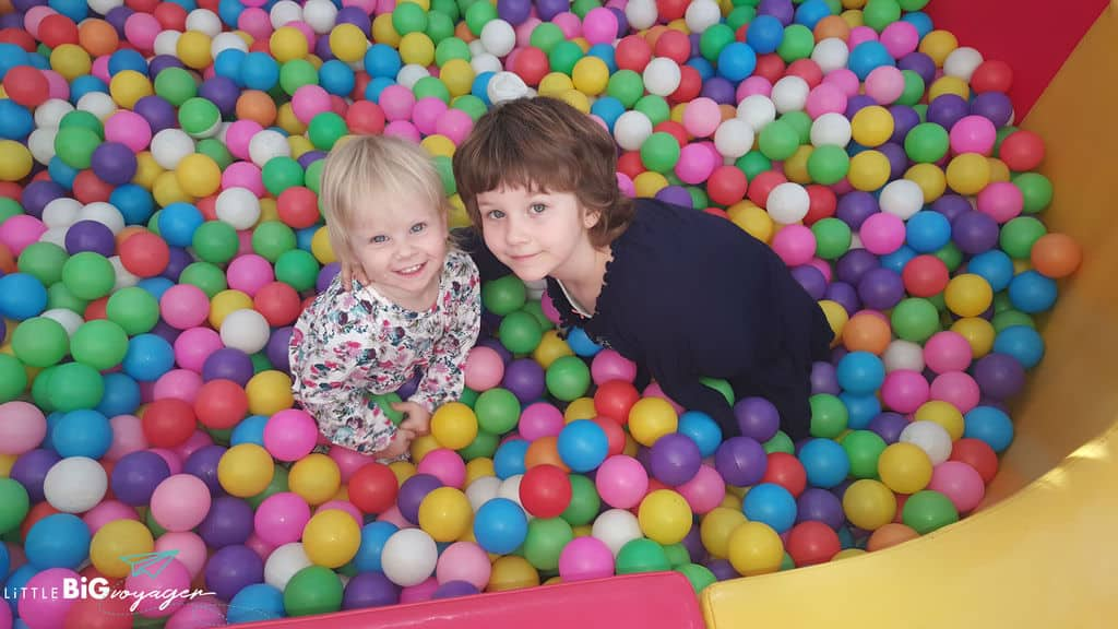 little J and big J in a ball bath at a play cafe in Providencia